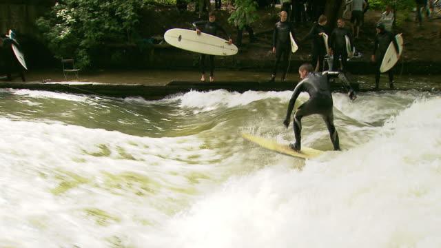englischer garten - eisbach, surfer on water, water, trees, viewer - surfen stock-videos und b-roll-filmmaterial