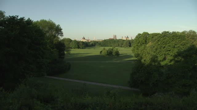 Englischer Garten,  lawn, trees, sun, blue sky, in background skyline of Munich