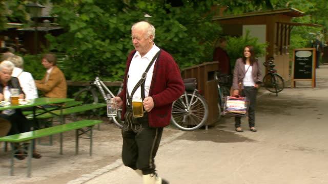 vídeos de stock, filmes e b-roll de englischer garten, man in traditional bavarian clothes with beer, biergarten, people sitting on benches - só um homem idoso
