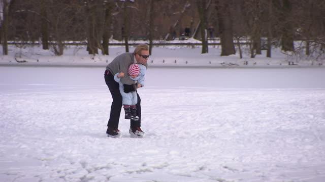 englischer garten, man with his child on ice skates, winter, snow - ミュンヘン エングリッシャーガルテン点の映像素材/bロール
