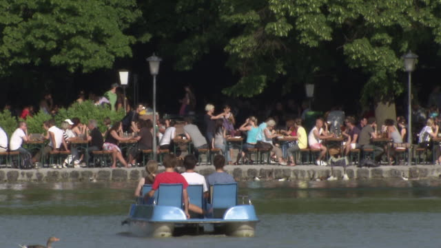 Englischer Garten - Seehaus, many people in Biergarten, some people ride a pedal boat, trees
