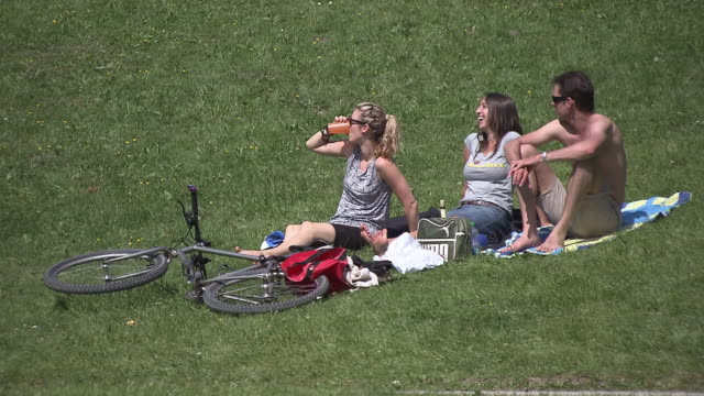 englischer garten, three people sitting on earth,  summer,  sunny, park, lawn, bike - ミュンヘン エングリッシャーガルテン点の映像素材/bロール