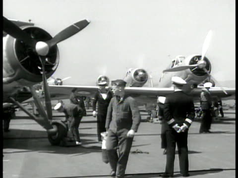 english aircraft carrier bi-plane taking off. fighter airplanes english crews on deck. vs men loading bombs onto wing removing tire block. fighter... - aircraft carrier stock videos & royalty-free footage