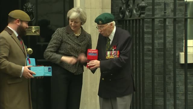 English and Scottish FA to defy FIFA over Armistice Day poppy wearing ENGLAND London Downing Street EXT Theresa May MP buying a poppy from veterans...