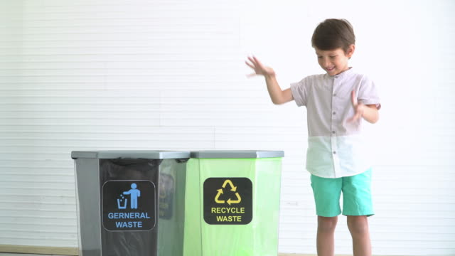 vídeos de stock e filmes b-roll de english boys seperate plastic bottle into recyclable bin - lixeira