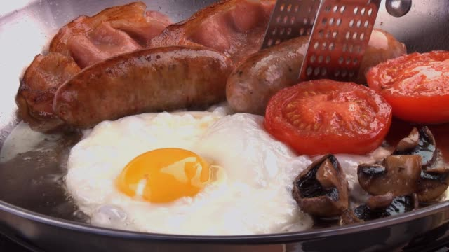 english breakfast: bacon, egg, sausage etc. in frying pan - sausage stock videos & royalty-free footage