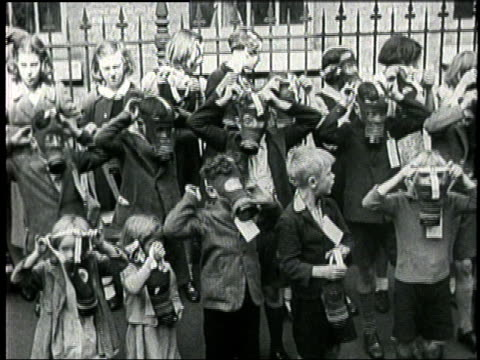 English children learn how to wear and operate gas masks