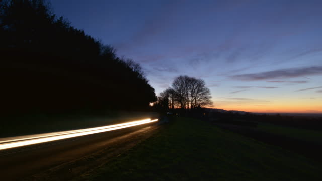english countryside in winter at sunset fast moving commuter traffic passes along a busy b road - headlight stock videos & royalty-free footage