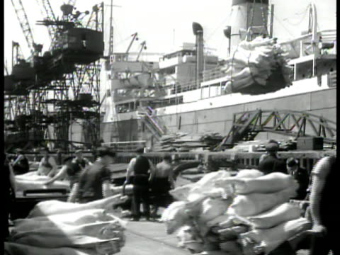 english dock workers unloading meat goods docked ship ha ws carting off processed meat ms workers unloading sacks la ms bow of ship in dock wwii - unloading stock videos & royalty-free footage