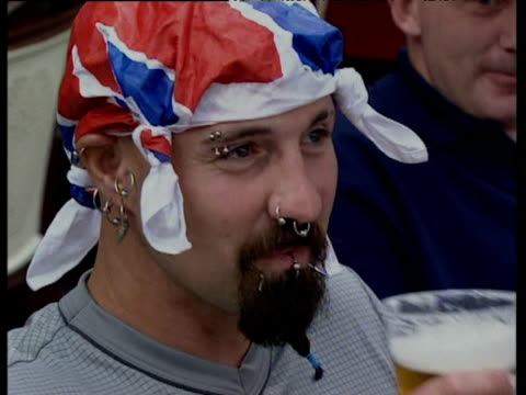 english football fan with facial piercings and union jack handkerchief on head drinks beer outside cafe during european championship finals... - internationaler fußball stock-videos und b-roll-filmmaterial