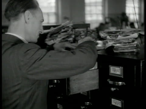 english man at filing cabinet cu hands flipping through files - filing cabinet stock videos & royalty-free footage