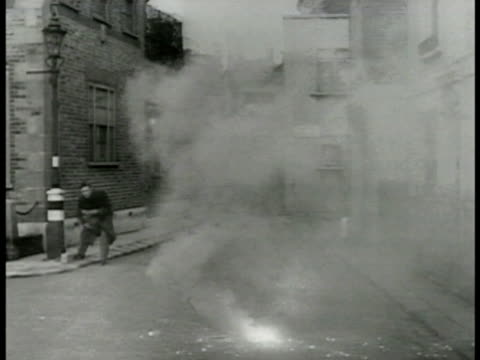 english man incendiary bomb on street runs picks up sandbag ms incendiary bomb sparks vs man w/ sandbag held up to face drops sandbag on top of bomb... - sandbag stock videos and b-roll footage