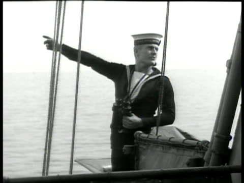 english navy flag. sailor on deck pointing. trawler convoy at sea. minesweeper ship w/ line in water. line of trawlers. . wwii floating mines - ship stock videos & royalty-free footage