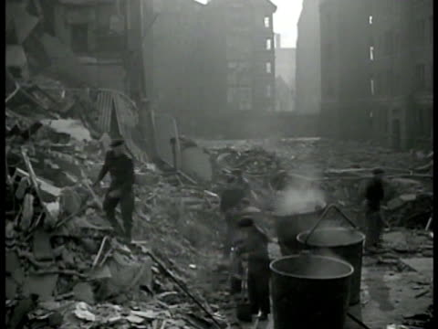 English people going through clearing rubble of bombed area smoke MS Men removing body of dead woman from debris into bag WWII World War II bombing...
