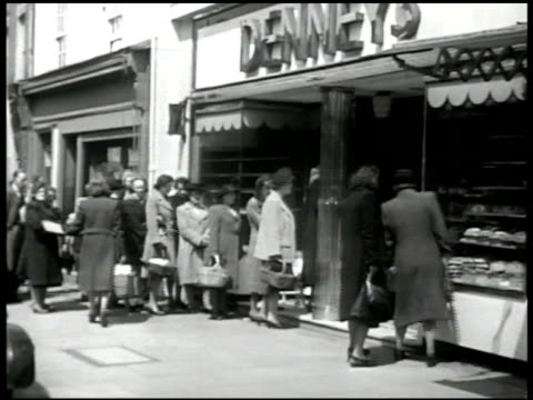 english people on street waiting in line in front of bread store cu loaves of bread in window vs people in line cu sign 'no cigarettes' post world... - food stamps stock videos & royalty-free footage