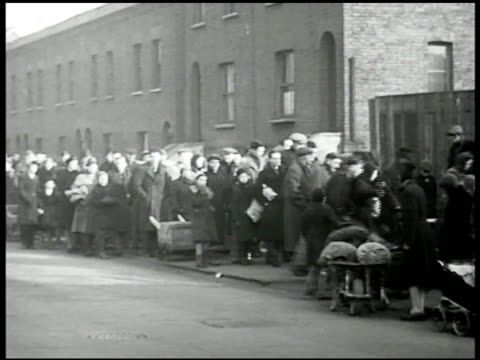 english people waiting in line on street ws people w/ wheel barrels passing entering coal yard ms man pouring coal into open bag held by man post... - food stamps stock videos & royalty-free footage
