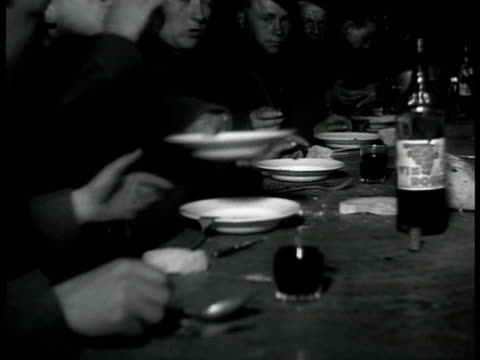 English soldiers in room some playing checkers some drinking talking MS Soldier playing harmonica Soldiers sitting at tables passing plates down man...