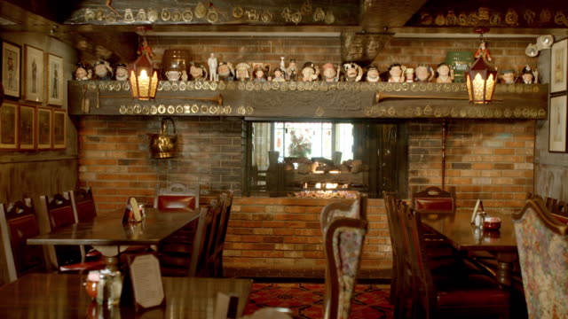 ws ts english traditional restaurant with open fireplace and collection of toby mugs on mantle - abandoned stock videos & royalty-free footage