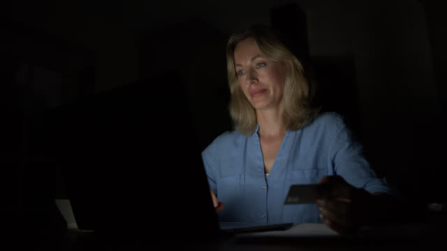 english woman at home shopping online late at night using her laptop and credit card - dark stock videos & royalty-free footage