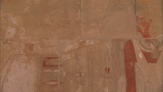 engravings depicting pharaoh hatshepsut 's mother ahmose cover the side of an ancient stone temple at deir el-bahari egypt. available in hd. - tempio di hatshepsut video stock e b–roll