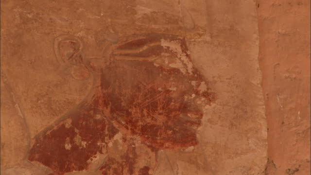 Engravings depicting the Egyptian Pharaoh Hatshepsut cover the side of an ancient stone temple at Deir el-Bahari Egypt. Available in HD.