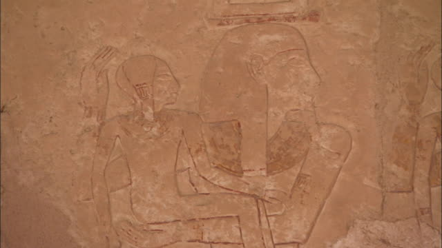 engravings of an egyptian family cover the side of an ancient stone temple at deir el-bahari egypt. available in hd. - hatschepsut tempel stock-videos und b-roll-filmmaterial