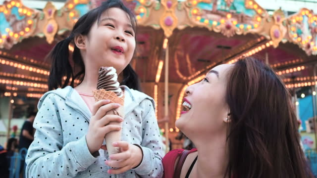 enjoy amusement fun park concept.asian mother and daughter eating ice cream in an amusement park and a carousel background. - roundabout stock videos & royalty-free footage