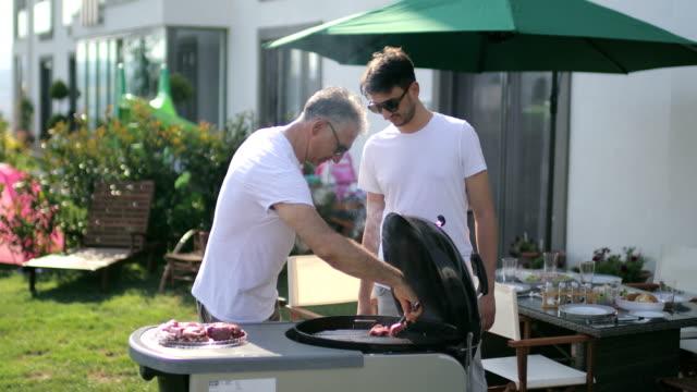 vidéos et rushes de profiter d'un barbecue avec la famille dans la cour arrière, le père et le fils ayant barbecue dans la cour arrière - barbecue