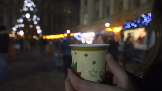 stockvideo's en b-roll-footage met genieten van een warm drankje in de kerstmarkt. - koffie drank