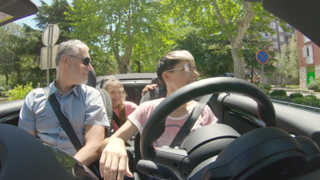 enjoying a ride with a convertible car around a mediterranean small town - family convertible stock videos & royalty-free footage