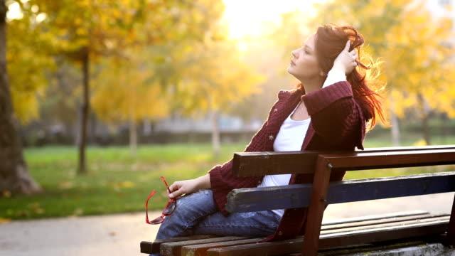 vídeos de stock e filmes b-roll de enjoying autumn woman on park bench - banco de parque