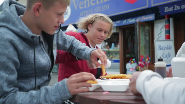 enjoying fish and chips - teenage boys stock videos & royalty-free footage