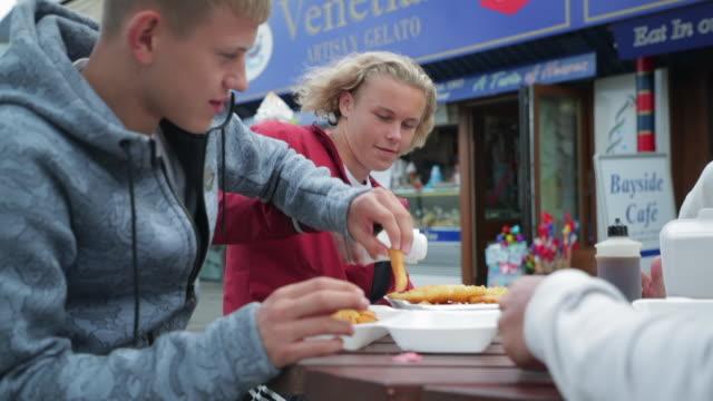 stockvideo's en b-roll-footage met genieten van fish and chips - een dag uit het leven serie