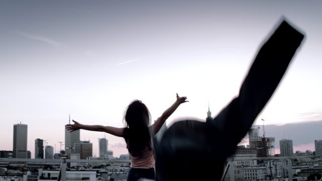 enjoying freedom, rooftop city view - adulto video stock e b–roll
