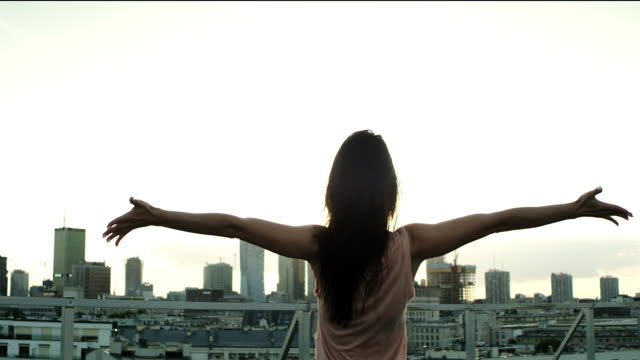 enjoying freedom, rooftop city view - lanciare video stock e b–roll