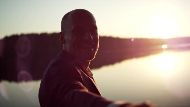 Enjoying lake sunset. Businessman on a pier