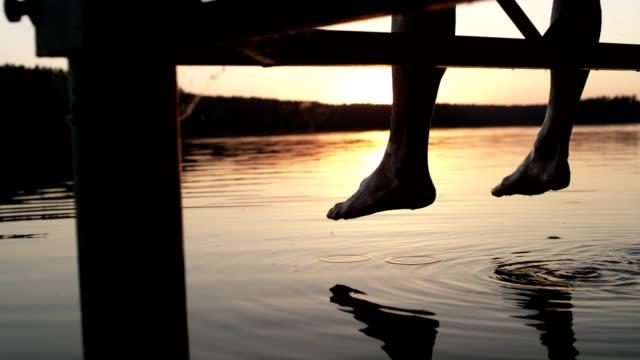 Enjoying lake sunset. Man sitting on a pier