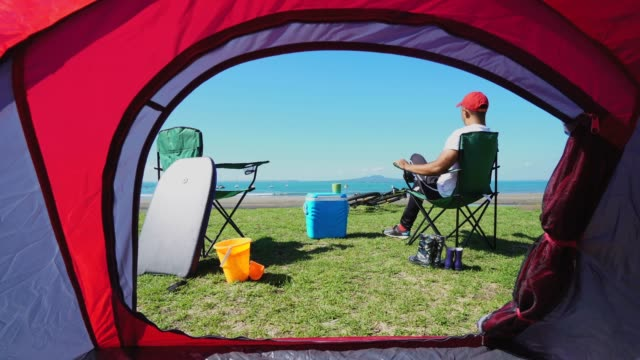 enjoying outdoors at beach. - tent stock videos & royalty-free footage