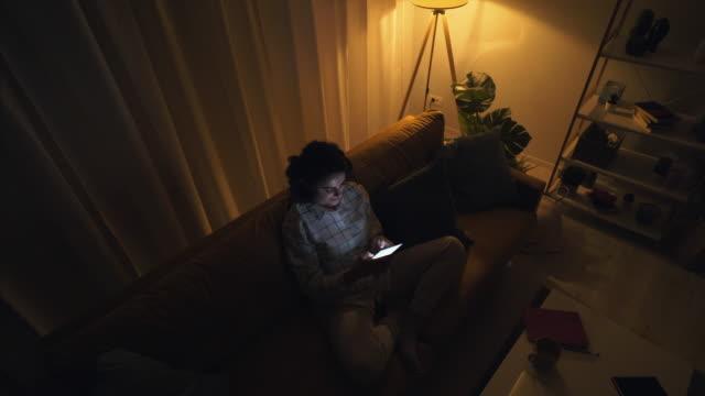vídeos de stock e filmes b-roll de enjoying some browsing late in night. - sala de estar