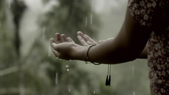 vidéos et rushes de profiter de la pluie estivale. atteindre pour les gouttes d'eau - goutte de pluie