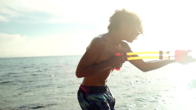 enjoying summer vacation on the beach - squirt gun stock videos and b-roll footage