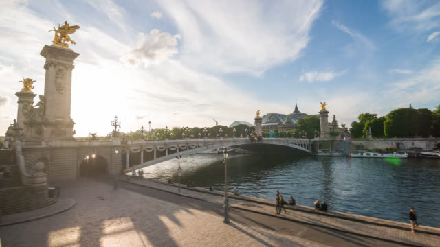 enjoying sunny day in paris by pont alexandre iii bridge over seine river with grand palais in the background - river seine stock videos & royalty-free footage
