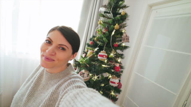 enjoying taking selfie near the christmas tree. - photograph stock videos & royalty-free footage