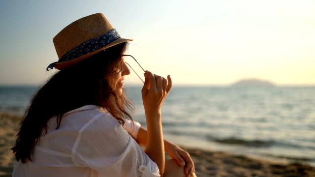 stockvideo's en b-roll-footage met genieten van de strandvakantie - zonnehoed hoed