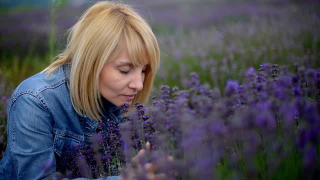 Enjoying the scent and freshness, elegant blonde female in lavender fields.