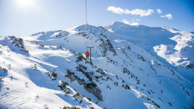 enjoying the view at the mountains while riding on a chairlift at a ski resort on a sunny day - inquadratura dalla sciovia video stock e b–roll