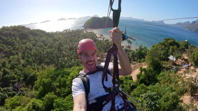 enjoying the zip line above the sea in el nido, palawan, philippines - sports helmet stock videos & royalty-free footage