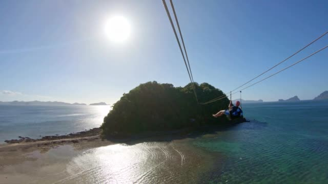 enjoying the zip line above the sea in el nido, palawan, philippines - zip line stock videos & royalty-free footage