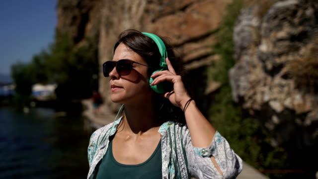vídeos de stock, filmes e b-roll de aproveitando a caminhada. música de escuta da menina em auscultadores ao ar livre, andando no por do sol - óculos escuros acessório ocular