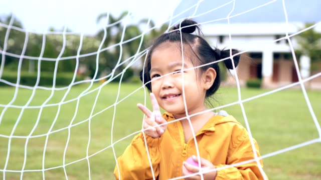 enjoyment happiness time of Asian child/girl in soccer goal